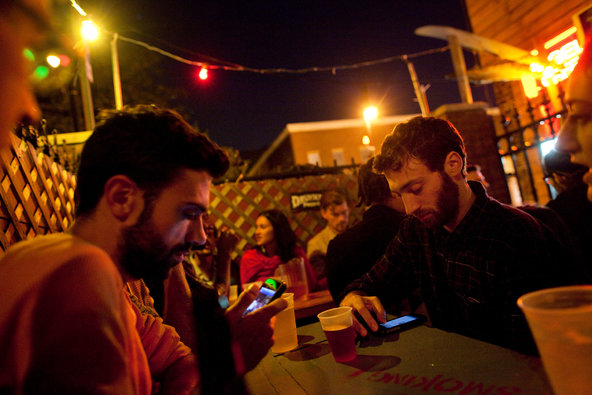 People using Mobiles in Bar